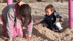 Girl and toddler are playing with heap of stones Stock Footage