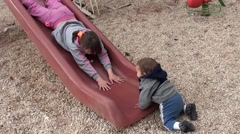 Girl and toddler play on slide Stock Footage