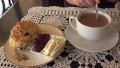 Tea and scones with jam and cream, woman stirs tea in cup Stock Footage