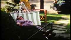 1830 - grandmother takes a nap in the hammock - vintage film home movie - stock footage
