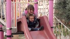 Three children play on slide Stock Footage