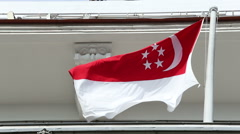 Singapore flag waves in wind from flagpole on top of buliding Stock Footage