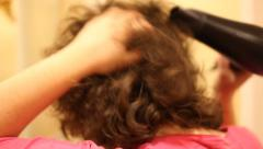Young woman dries the hair dryer Stock Footage