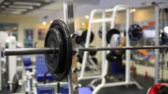 Brown hair athlete is putting weight plate on the barbell. Stock Footage