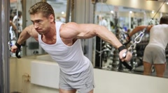 Bodybuilder does shoulders exercises against mirror Stock Footage