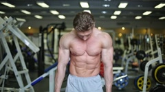 bodybuilder poses demonstrating tense muscles in gym hall. - stock footage