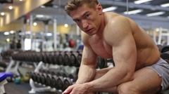 Brown hair bodybuilder man has rest sitting in gym hall. Stock Footage