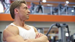 Bodybuilder stands with his arms crossed on chest in gym hall. Stock Footage