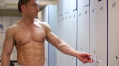 Bodybuilder opens door in locker room after finishing training. Stock Footage