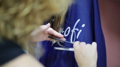 The barber with comb and scissors is cutting long wet hair. Stock Footage