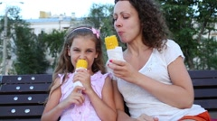 A mother and daughter sitting on the bench, eating boiled corn. Stock Footage