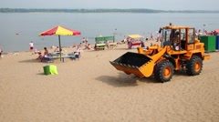 Tractor is going on the sandy beach of river Volga. Stock Footage