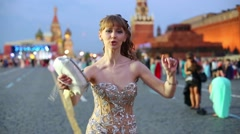 Smiling girl in a beautiful dress is dancing on Red Square. Stock Footage