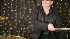 Drummer in glasses and hat plays drum set at studio with garlands Stock Footage