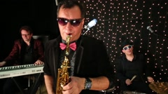 Three musicians are playing on the scene with garlands. Stock Footage