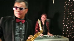Close up view of four musicians in black studio with garlands. Stock Footage