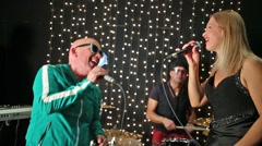 Two men and girl are singing in the black studio with garlands. Stock Footage