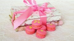 Rose macaroons on table with books wrapped ribbon. Stock Footage