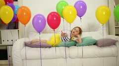 Little girl laying at big sofa in room with carpet on floor Stock Footage