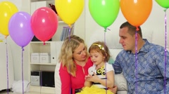 Family sits on floor in light room behind row birthday balloons Stock Footage