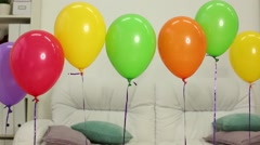 Interior of room with sofa and row balloons hanging in air. Stock Footage