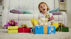 Little girl sits with gift boxes and birthday air balloons Stock Footage