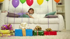 Little girl laying on the sofa behind birthday air balloons. Arkistovideo