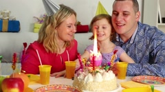 Family sits at birthday table and looks to burning candle on cake - stock footage
