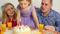 Family sits at birthday table, daughter blows out candle on cake - stock footage