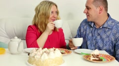 Young couple is talking and sitting on sofa at the birthday table Stock Footage