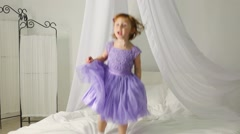 Little girl in dress is jumping on the bed with white baldachin. Stock Footage