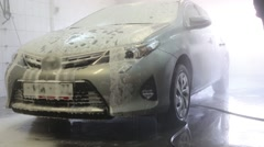 Worker is cleaning gray car in the carwash service. Stock Footage