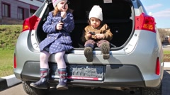 Two children are sitting in the open trunk of car. Stock Footage
