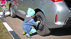Little girl and boy tie rear wheel of car with socket wrench. Stock Footage