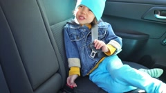 Little boy in a jeans jacket is sitting at the car. Stock Footage