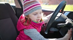 Little girl in waistcoat and striped hat sitting at wheel of car. Stock Footage