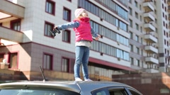 Little girl is standing on car roof with open hands. Stock Footage