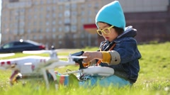 Little boy sitting with radio control in hands and quadcopter. Stock Footage