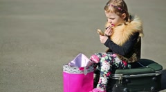 Little girl sitting on suitcase in middle of road, painting lips Stock Footage