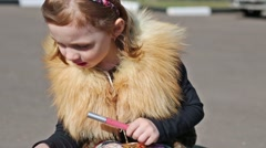 Little girl with a lipstick is sitting in the street. Stock Footage