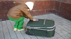 Little boy is opening green suitcase on the street. Stock Footage