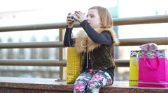 Little girl with a camera is sitting on the street. Stock Footage