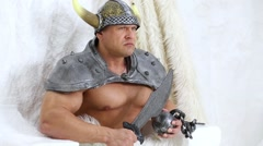 Spiteful viking with sword in hand and helmet on head among furs. Stock Footage