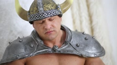 Muscular man in viking costume raises up dragon skull slowly. Stock Footage