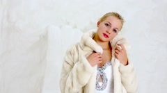 Young woman stands near to icy wall wrapping herself in fur coat. Stock Footage