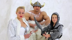 Viking family stands under icy wall, slightly powdered with snow. Stock Footage