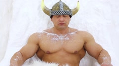 Muscular man dressed in viking costume sits under icy wall Stock Footage