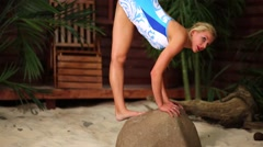 Girl in swimsuit does vertical split  on the stone at sandy beach. Stock Footage