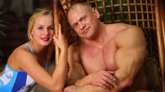 Tanned muscular man and girl in swimsuit near wooden house. Stock Footage