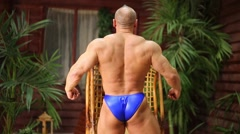 Bodybuilder demonstrates his muscles standing back near bungalow. Stock Footage